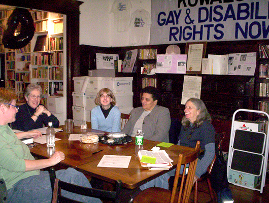 Five Lesbians sitting around a table inside the Lesbian Herstory Archives. They are smiling and engaged in conversation.