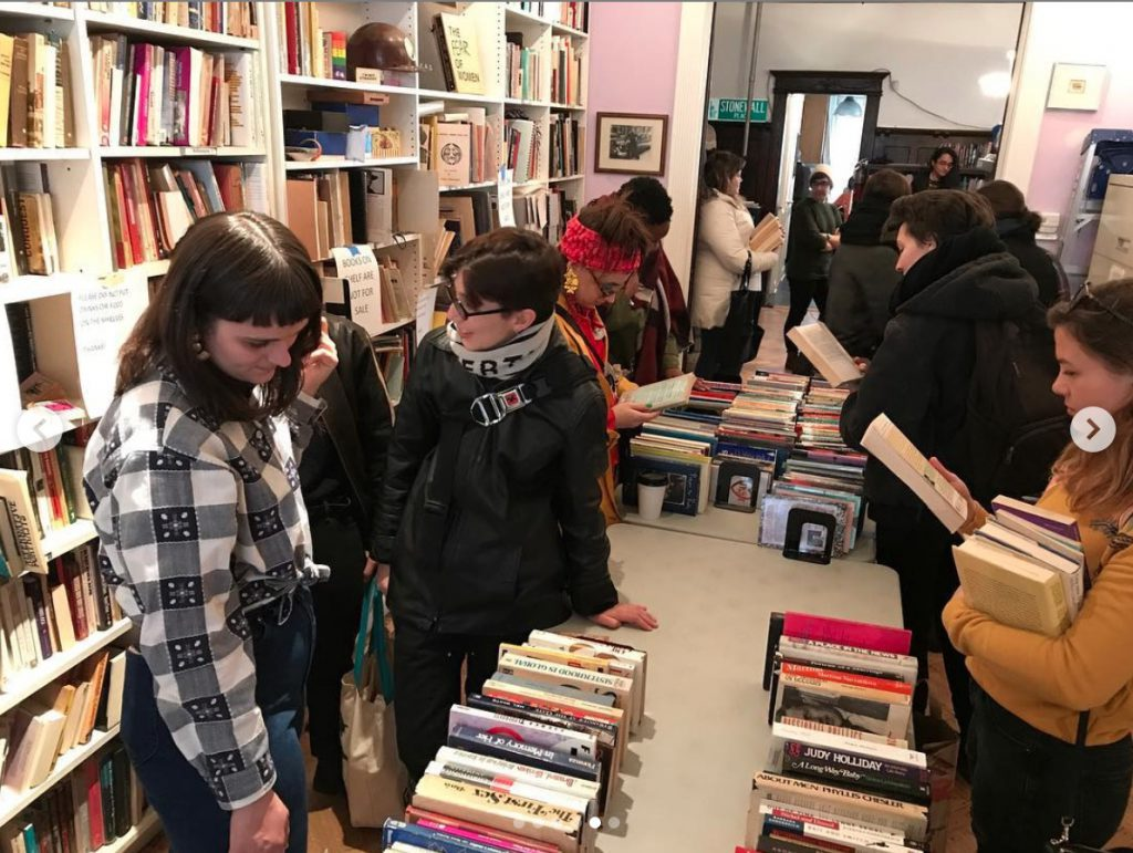 Visitors look through books displayed along both sides of a row of tables. Shelves full of books line the room.