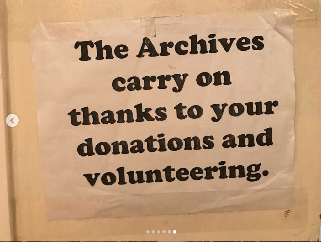 "A paper sign taped to a wall that reads ""The Archives carry on thanks to your donations and volunteering."""