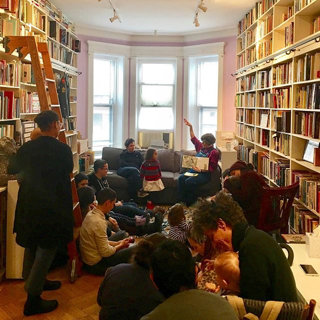 A group of adults and children are gathered on the floor of a room lined with bookshelves. A Lesbian sitting on a couch at the end of the room is reading a children's book to the group.