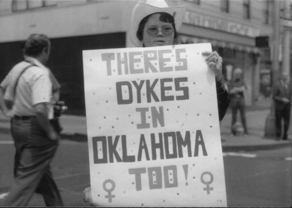 """A Lesbian holding a large sign that reads """"There's Dykes in Oklahoma Too!"""""""