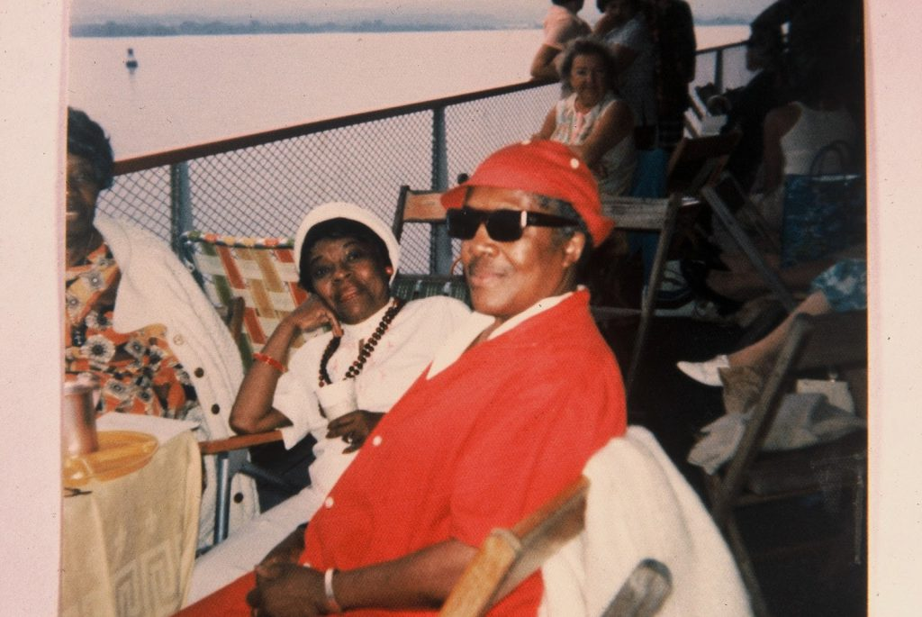 Two Black Lesbians sitting in chairs on a boat deck. They are smiling and appear to be in relaxed postures.