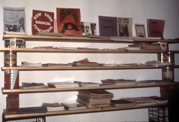 A homemade shelf containing stacks of periodicals.