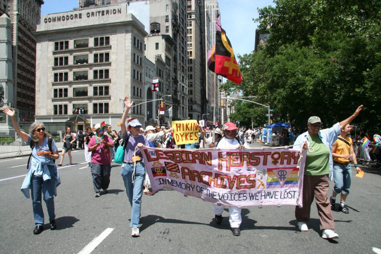Lesbian Herstory Archives Coordinators Hold a sign during a march