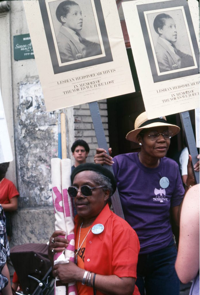 """Two Black Lesbians among a group holding signs that read """"Lesbian Herstory Archives: In Memory of the Voices We Have Lost."""""""