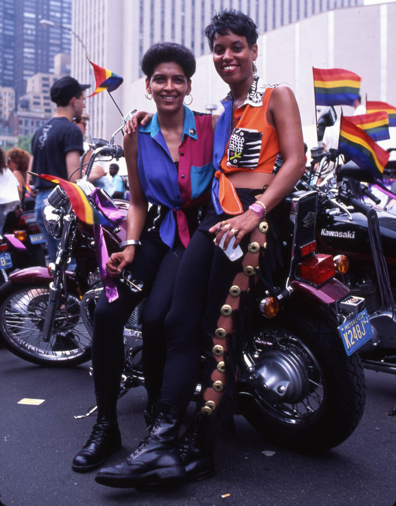 Two smiling dykes of color surrounded by pride flags sitting on a motorcycle at the dykes on bikes march.