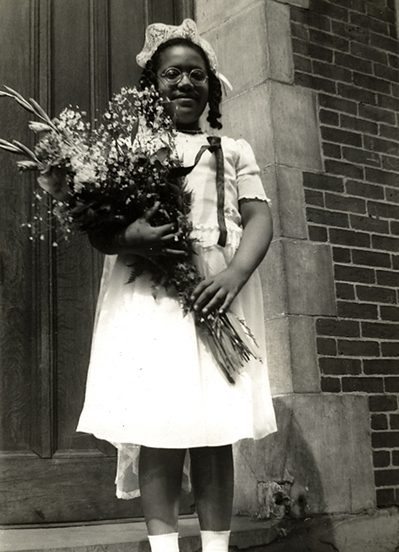 Audre Lorde as a young girl in a communion dress, holding a bouquet of flowers and standing on the steps in front of a door.