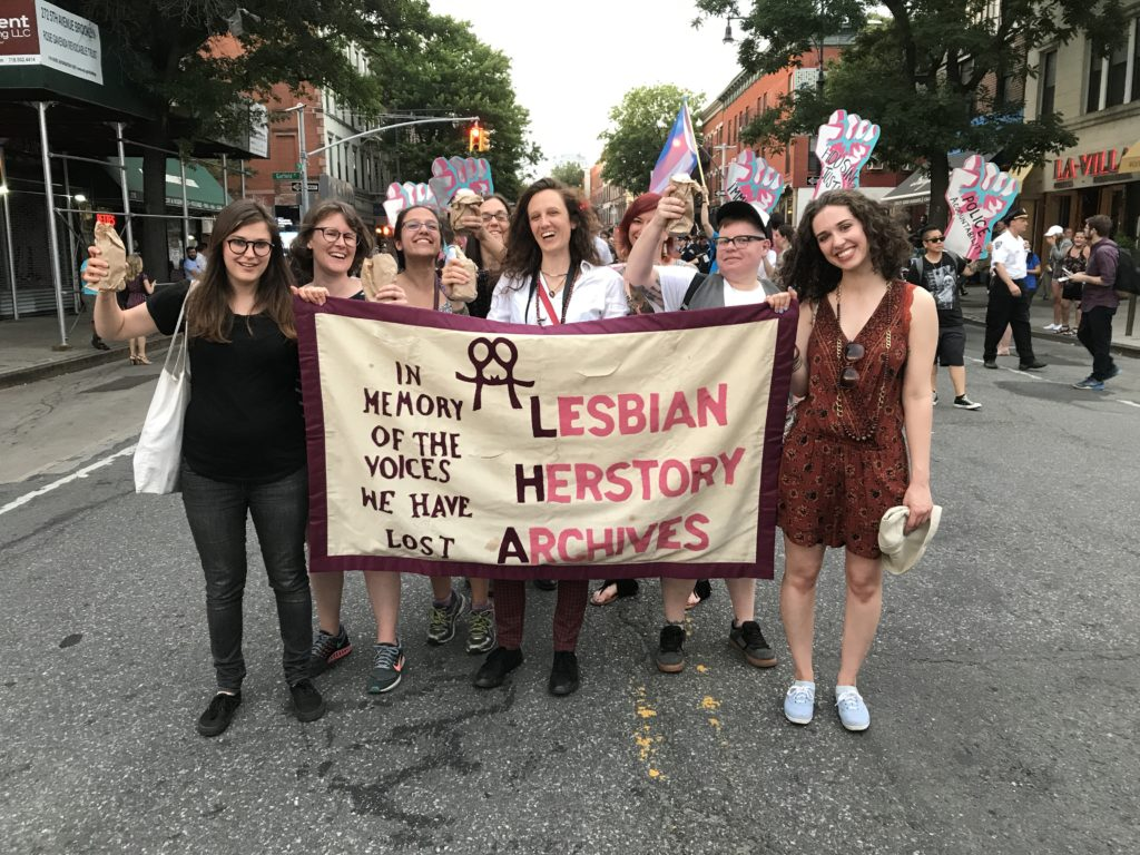 """A group of Lesbians at a march holding a banner that reads """"Lesbian Herstory Archives: In Memory of the Voices We Have Lost."""""""