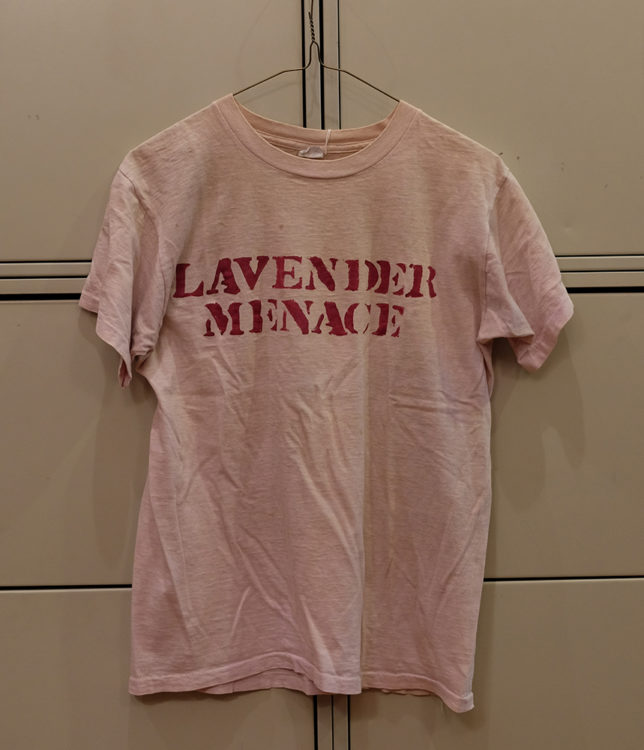 "Pink t-shirt that reads ""Lavender Menace"" in red stenciled font."
