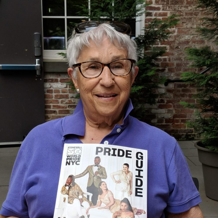 Headshot of a lesbian holding a magazine titled Pride Guide.