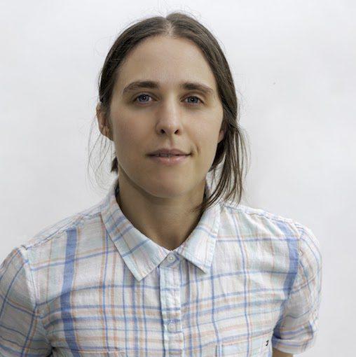 Headshot of a lesbian wearing a plaid shirt.