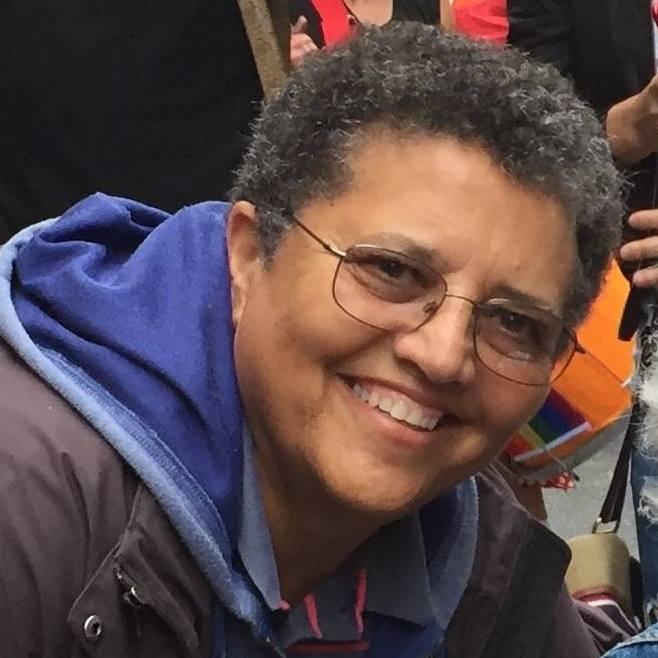 Headshot of a broadly smiling lesbian.