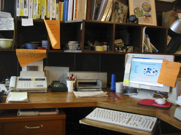 Workspace with an old computer on the desk, behind it are full shelves of books and objects