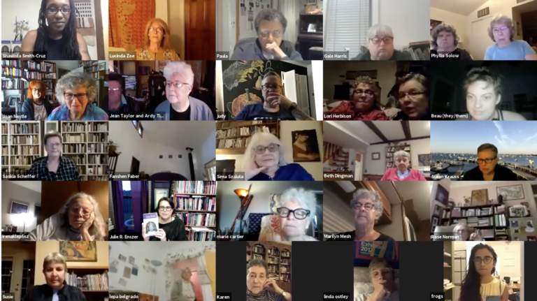 A screenshot from the live Zoom event celebrating the launch event for Sinister Wisdom volume 118, celebrating the Lesbian Herstory Archive's 45th Anniversary. In the image you can see a 5x5 grid of video images of people participating in the event. Each video image has one or two faces of people, some smiling, some looking on expectantly. One of the boxes features Julie Enszer holding up a copy of the issue of Sinister Wisdom as she addresses the virtual crowd.